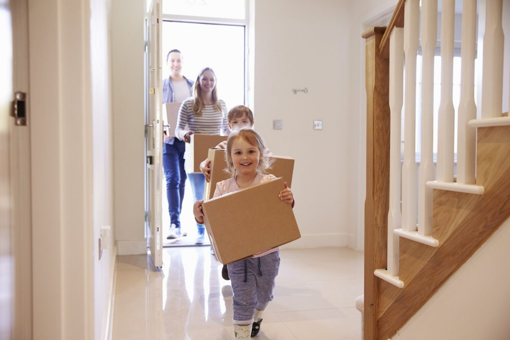 family carrying boxes into their new home