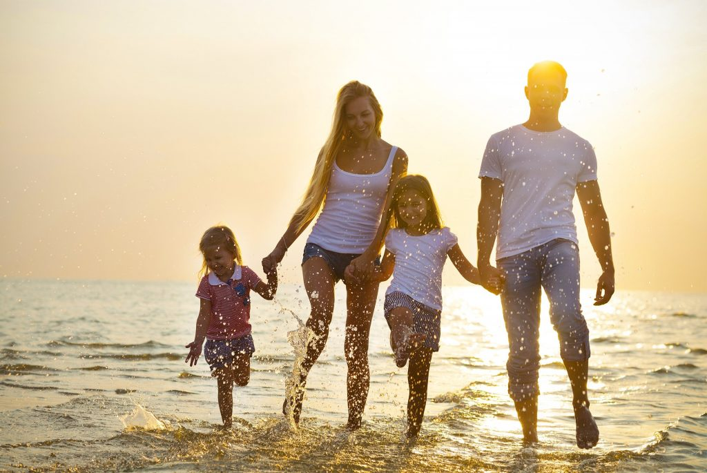 happy family (mum, dad and two children( holding hands and walking together through the waves at beach
