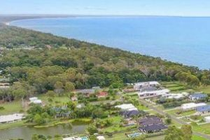 Arial view of Dundowran Beach suburb including beach, shrubbery & properties